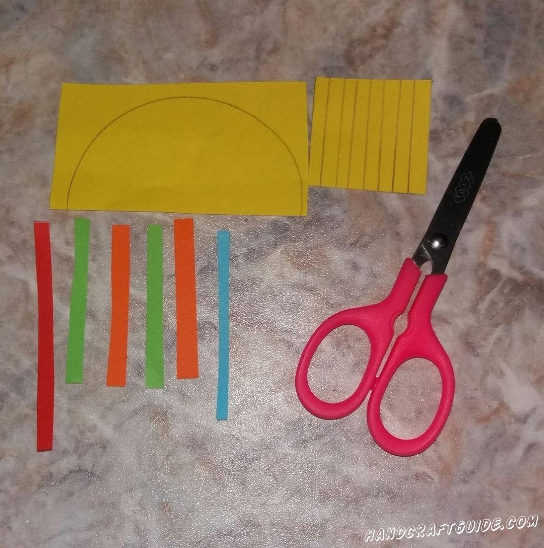 Для начала вырезаем все необходимые нам детали. Из желтой бумаги вырезаем желтый полукруг и 7 небольших полосочек. Затем вырезаем 2 зеленые полочки, 2 оранжевые, одну голубую и 1 красную. Голубая и красная полоски немного длиннее остальных, а желтые самые короткие