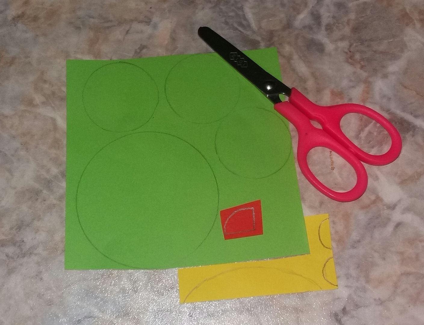Для начала берем зеленую бумагу и вырезаем 1 большой и 3 меньших круга. Затем вырезаем длинный полуовал и 2 полукруга желтого цвета. Ну и в конце подготовки вырезаем красную детальку, как показано на фото.