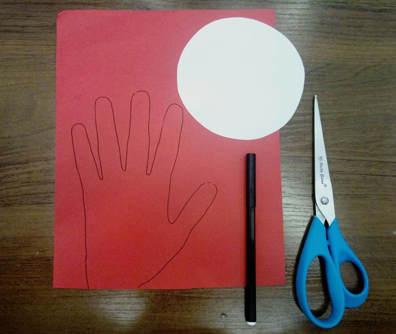 On the red A4 sheet, draw your palm along the contour. Then cut out the white circle as in the photo.