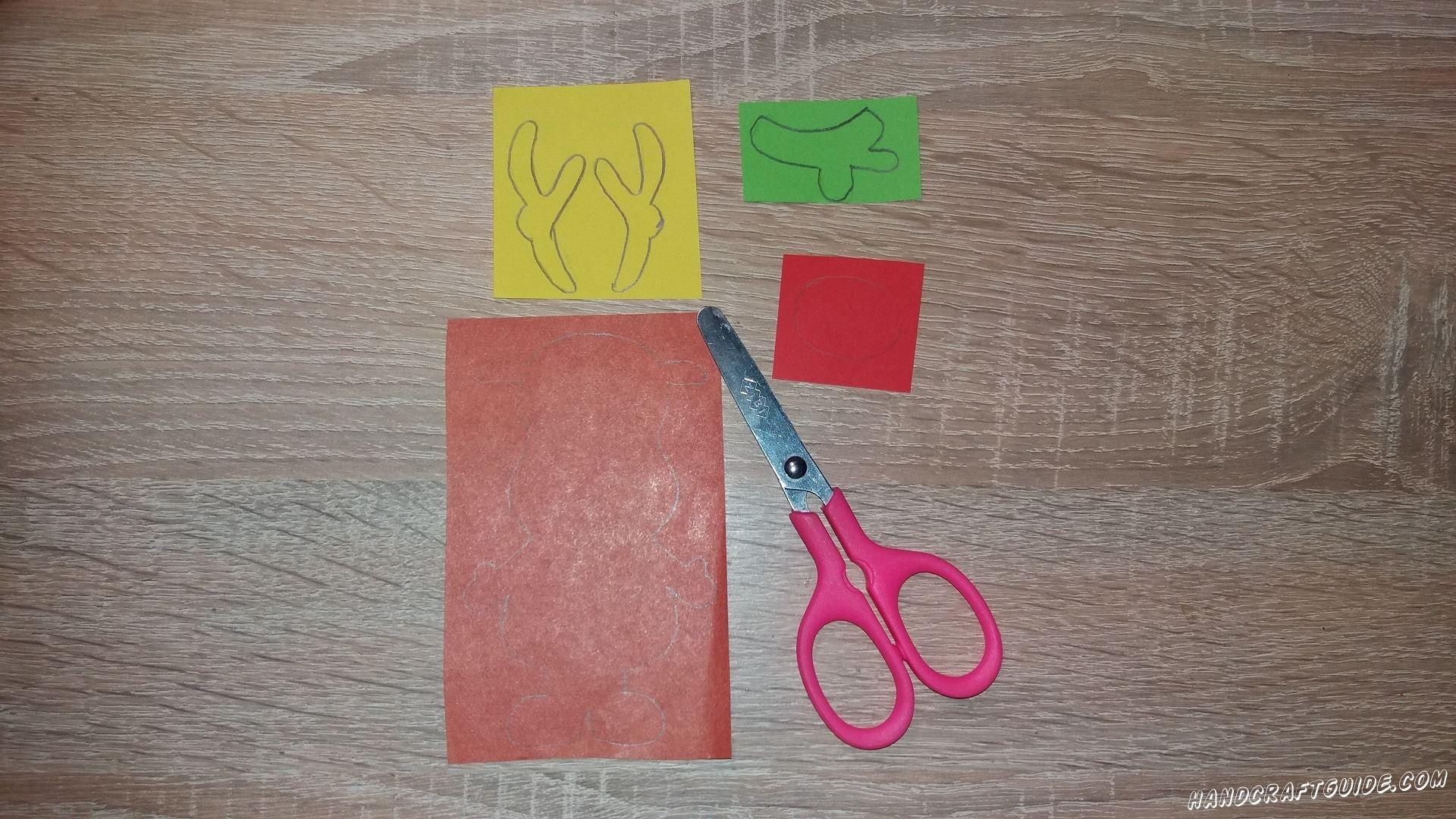 Для начала, на цветной бумаге, рисуем все необходимые нам фигурки: рожки желтого цвета, красный нос и зелёный шарф.  Из коричневой бумаги мы вырезаем основную часть, в неё входит тельце, голова, ушки и все лапки.
