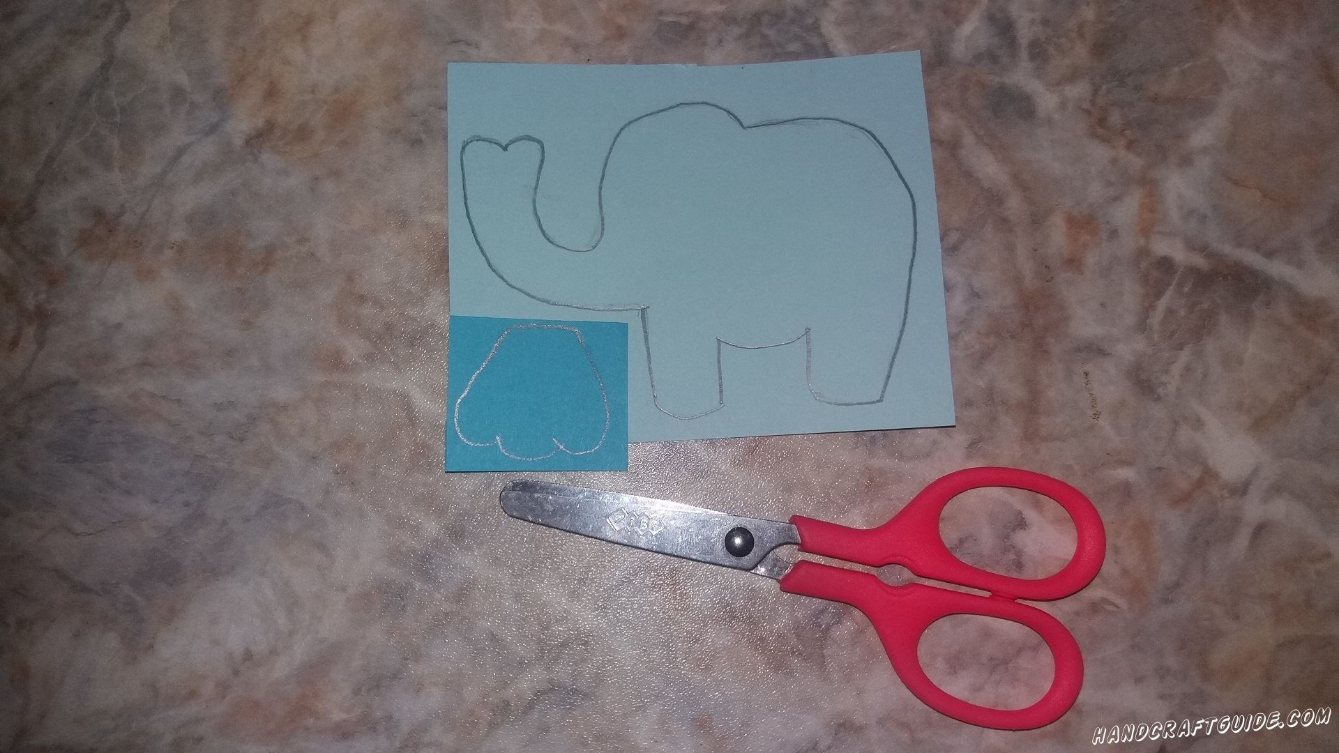 На голубом листе бумаги мы рисуем и вырезаем образ слона. На синей бумаге мы рисуем ушко слона и также вырезаем нарисованную картинку.