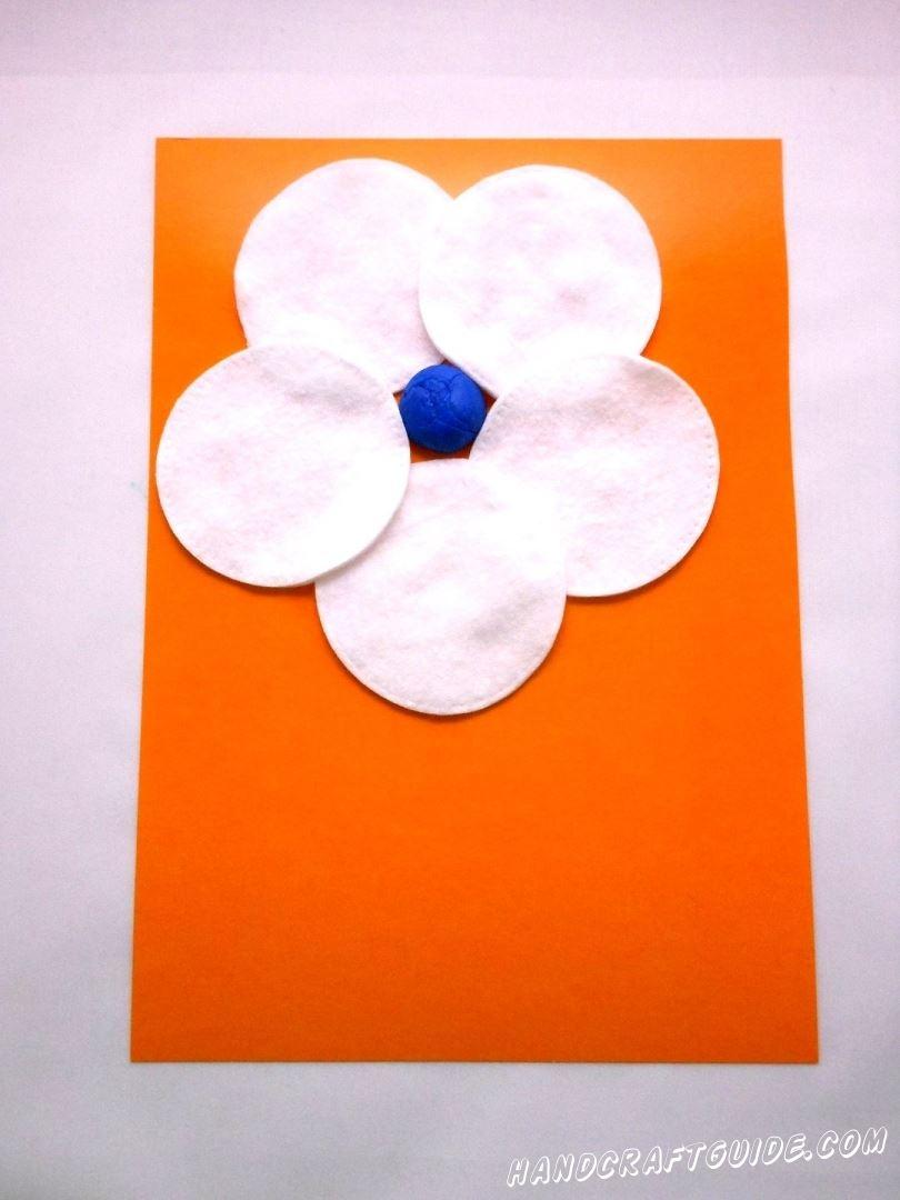 Выбираем лист картона любого цвета, который послужит нам фоном для нашей поделки. Теперь берем кусочек пластилина и скручиваем из него шарик. Прикрепим шарик на картон. Вокруг этого шарика приклеиваем лепестки цветочка – ватные диски.