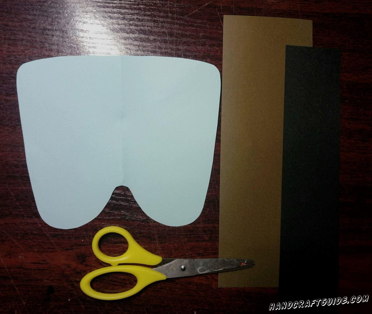 Для начала мы берем бумагу голубого цвета и вырезаем вот такой прямоугольник с закруглениями, как показано на фото.