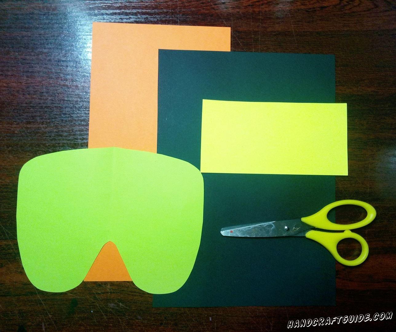 Берем бумагу салатового цвета и вырезаем основу нашей маски, как показано на фото