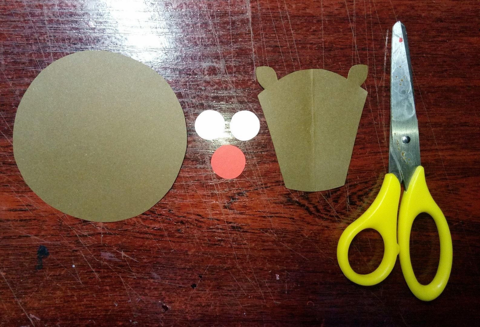 Вырезаем большой круг и фигурку головы с ушками оленя, из картона коричневого цвета. Также нам понадобится 2 малых кружка белого и, один чуть больший, красного цвета