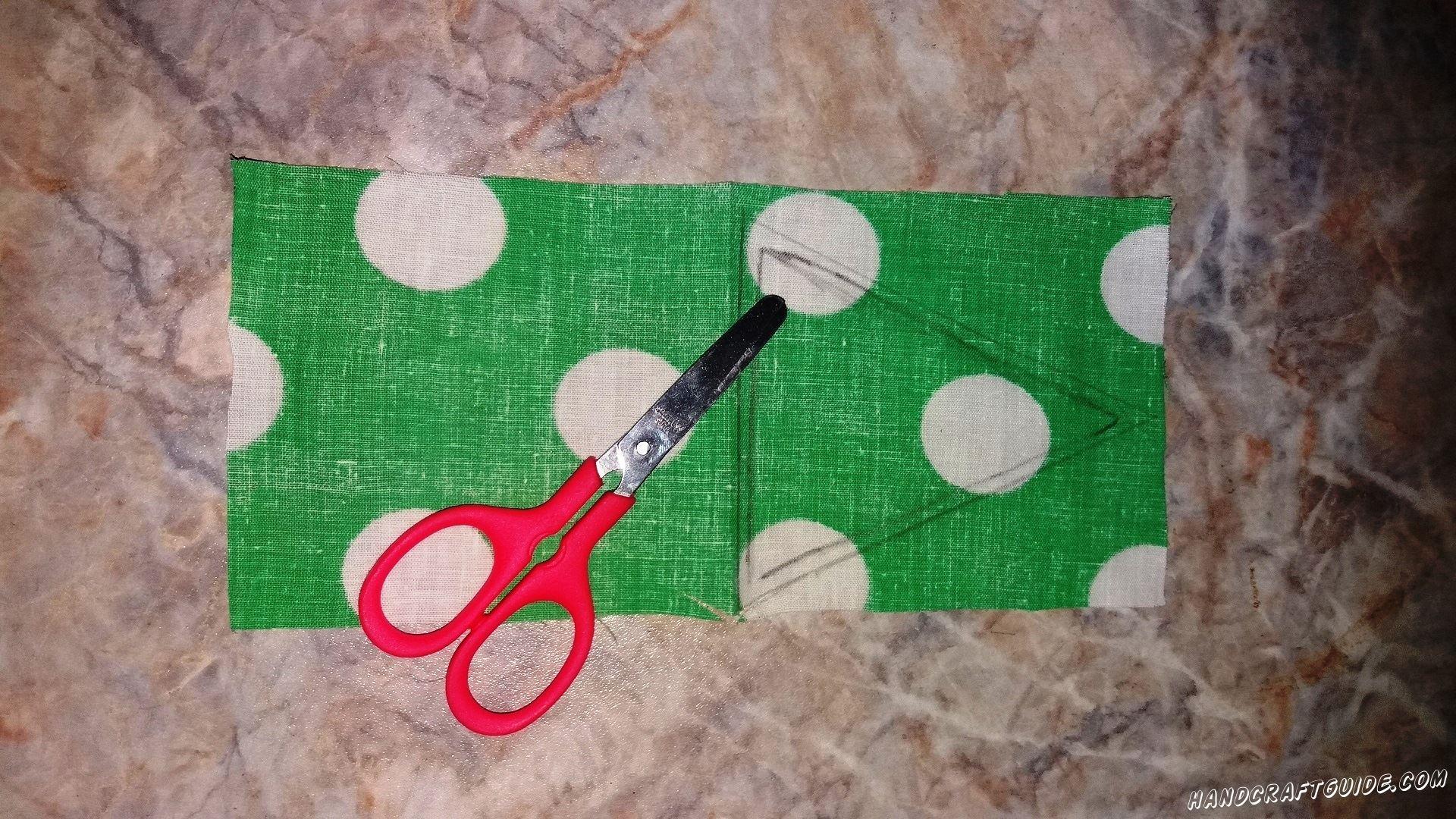 На одном кусочке ткани мы рисуем треугольник, складываем ткань пополам и вырезаем наш рисуночек. Получается 2 одинаковые детали.