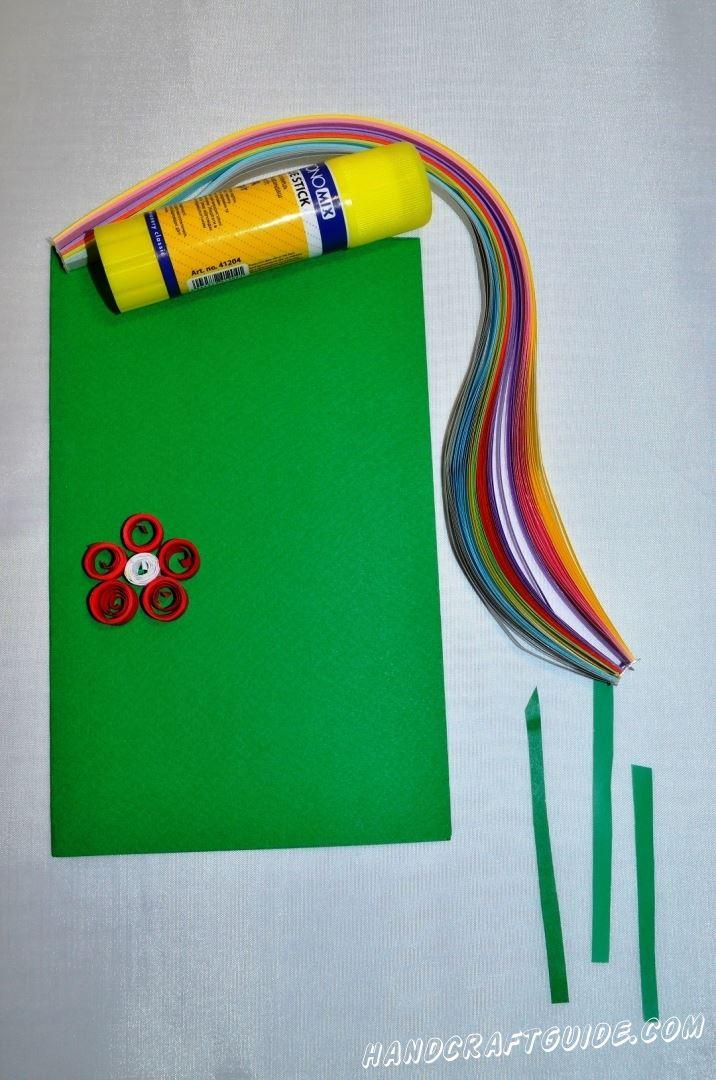 Размещаем перед собою зелёный лист бумаги в вертикальном положении. Теперь берем бумагу для квиллинга, и скручиваем  5 кружочков красного и 1 кружок белого цвета. Также отрезаем, обрезаем небольшие полосочки.