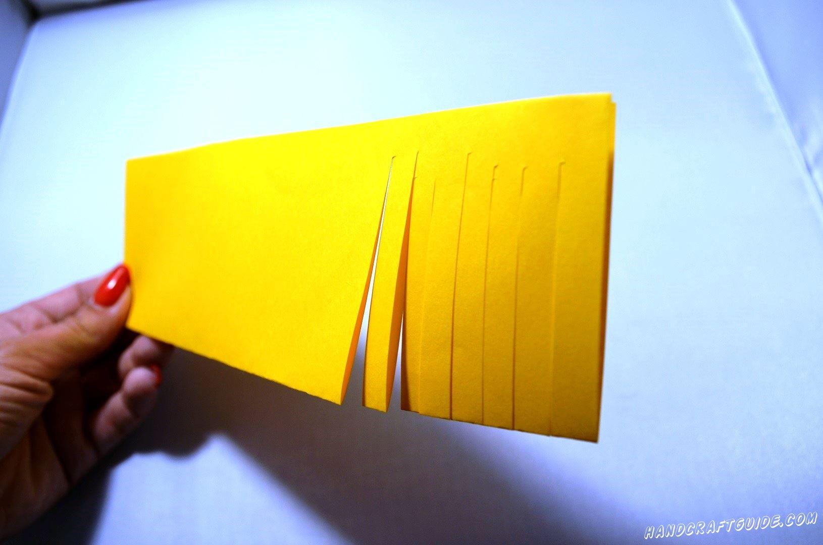 Берем лист желтой бумаги и складываем его вдоль пополам и начинаем делать надрезы со стороны сгиба и не до конца противоположной.