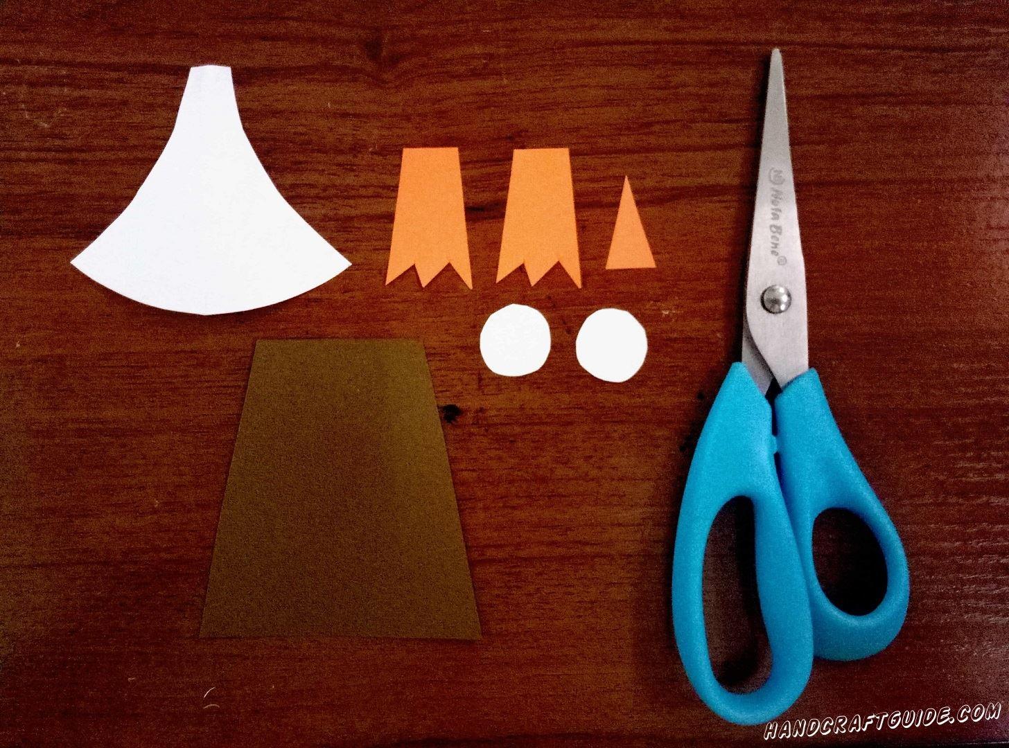 Для начала вырежем все, необходимые для работы, детали.Из коричневой бумаги вырезаем прямоугольник, который с одной стороны немного уже чем с другой. Затем берём белую бумагу, из нее мы вырезаем 2 кружочка, это будут глазки пингвина, и фигурку, напоминающую колокольчик, это будет животик пингвина. Ну и напоследок вырезаем 2 лапки и клювик из оранжевой бумаги.