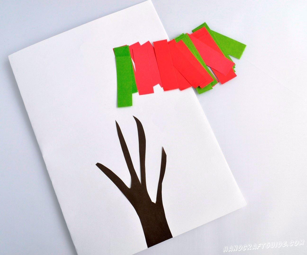 Для начала нам нужно вырезать все необходимые детали нашей поделки: фигурку в форме дерева коричневого цвета, и множество небольших полосок разными яркими цветами (мы выбрали зелёный и розовый). Дерево наклеиваем на белый лист бумаги.