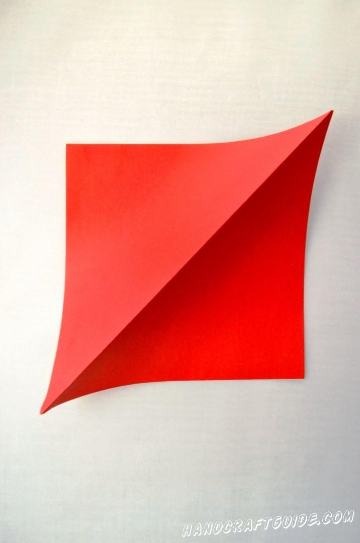 Берем квадратный цветной лист бумаги и делаем на нем сгиб, как показано на фото
