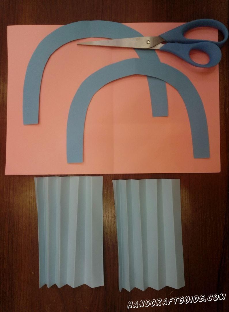 """Для начала возьмем голубую бумагу и вырежем 2 дуги одинакового размера. Затем из белой бумаги нам нужно 2 прямоугольника, их которых мы поочерёдным сгибанием сделаем """"гармошки""""."""
