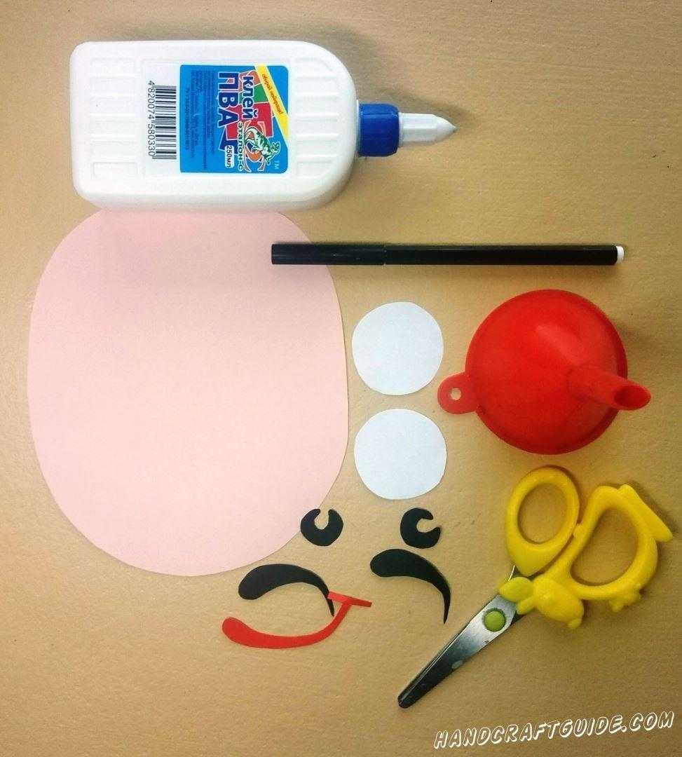 Сначала мы вырезаем все необходимые бумажные фигурки: основу лица розового цвета, два белых кружочка, чёрные брови и зрачки, а также улыбочку из красной бумаги.