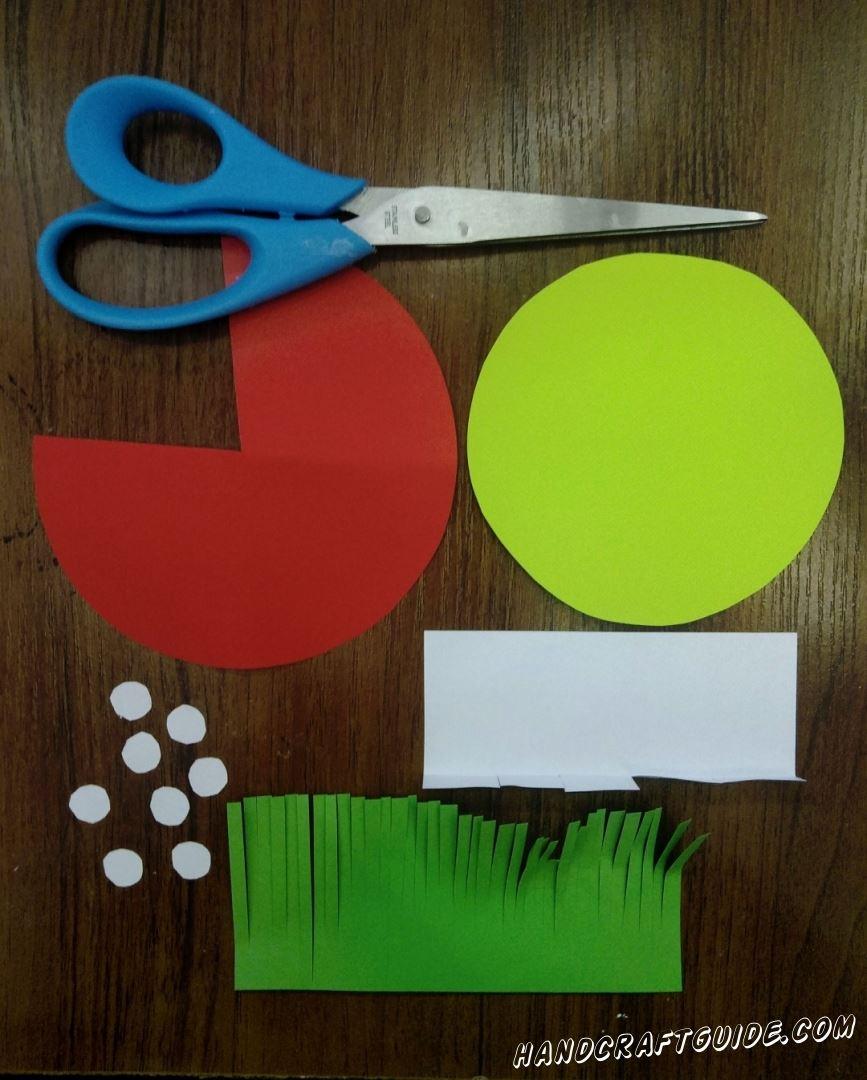 Для начала нам нужно вырезать, из цветной бумаги, все необходимые нам детальки. Возьмем красную бумагу и вырежем большой круг. Затем с этого круга вырезаем треугольник. Вырезаем еще один круг, немного меньшего размера, салатового цвета. Переходим к белой бумаге, с неё вырезаем небольшой прямоугольник и с одной стороны делаем надрезы, периодичностью в 1-2 см, и загинаем их вверх. Также вырезаем 8-10 маленьких беленьких кружочков. Ну и напоследок подготовки вырезаем прямоугольник зелёного цвета и с одной стор