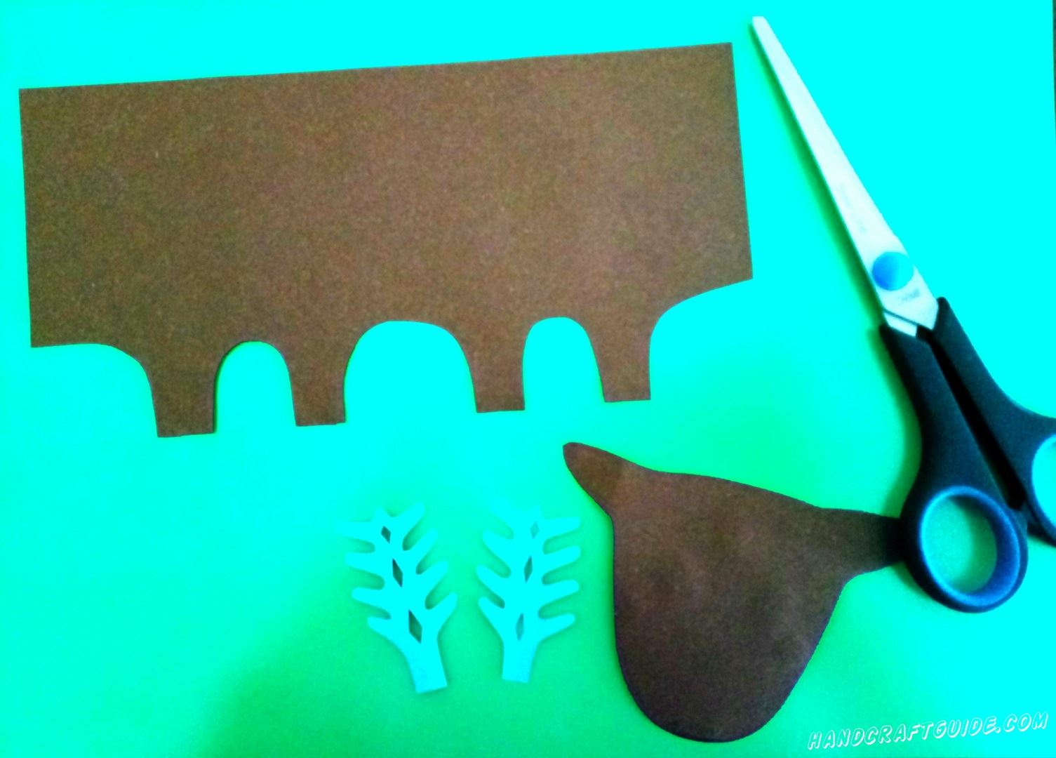 Cut out the head and trunk of brown paper. Then the horns are blue, as in the photo.