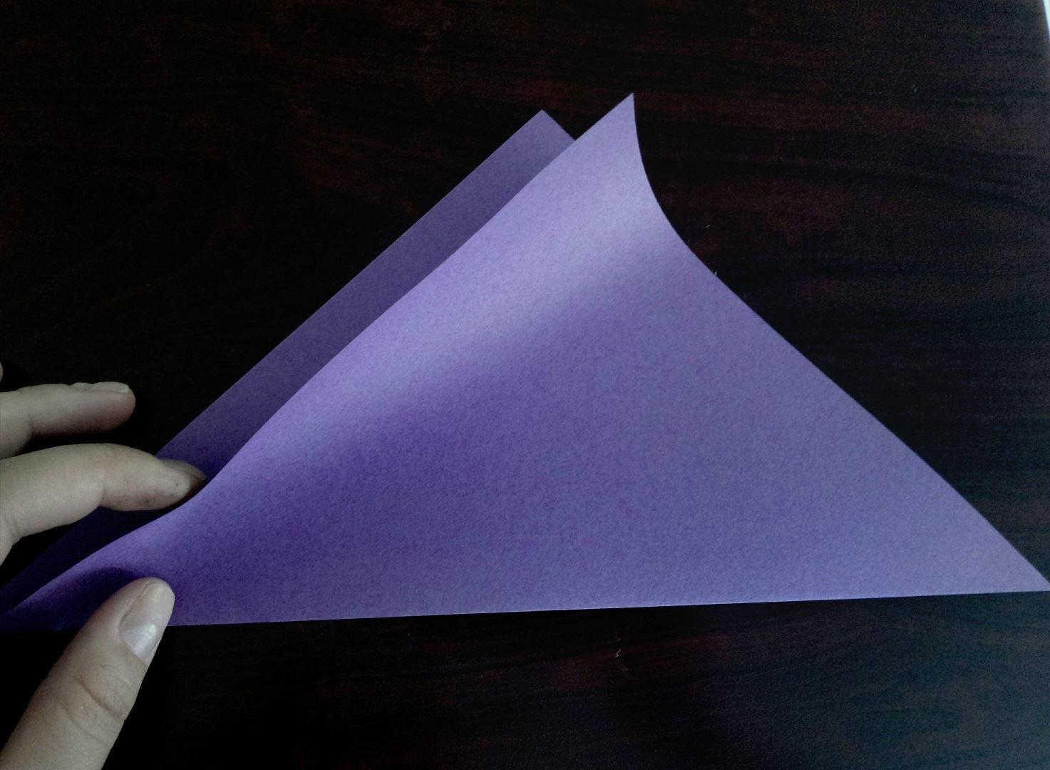 Сгибаем , лист бумаги квадратной формы , по диагонали пополам. Согните сложенный лист еще раз пополам, только совсем слегка, исключительно для того, чтобы наметить среднюю линию. Так вам будет легче в дальнейшем сделать мордочку кошки симметричной.