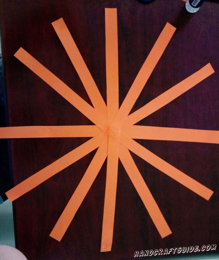Вырезаем 6 длинных полосок оранжевого цвета. Тоненькую, маленькую полосочку и кружок зелёного. Склеиваем полосочки в одной общей точке