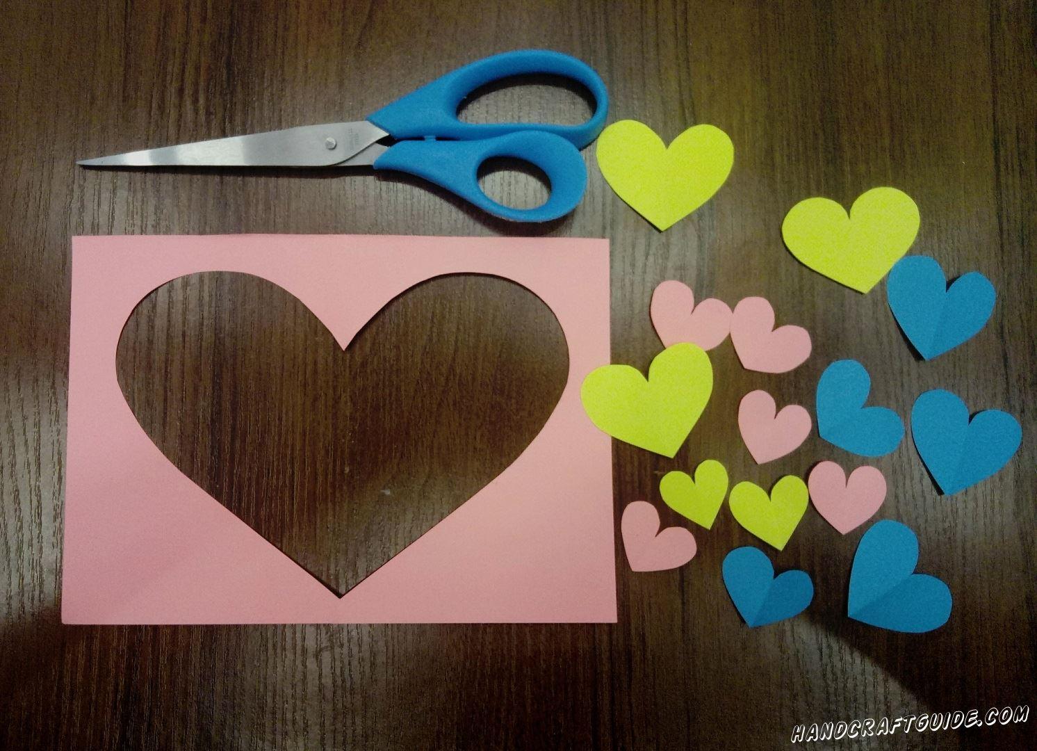 Для начала подготовим все нужные детальки. Берем лист розовой бумаги и складываем его пополам. На сгибе вырезаем детально как половина сердечка. Вырез должен быть почти на всю высоту согнутого листка. Затем вырезаем много сердечек, разного размера и цвета