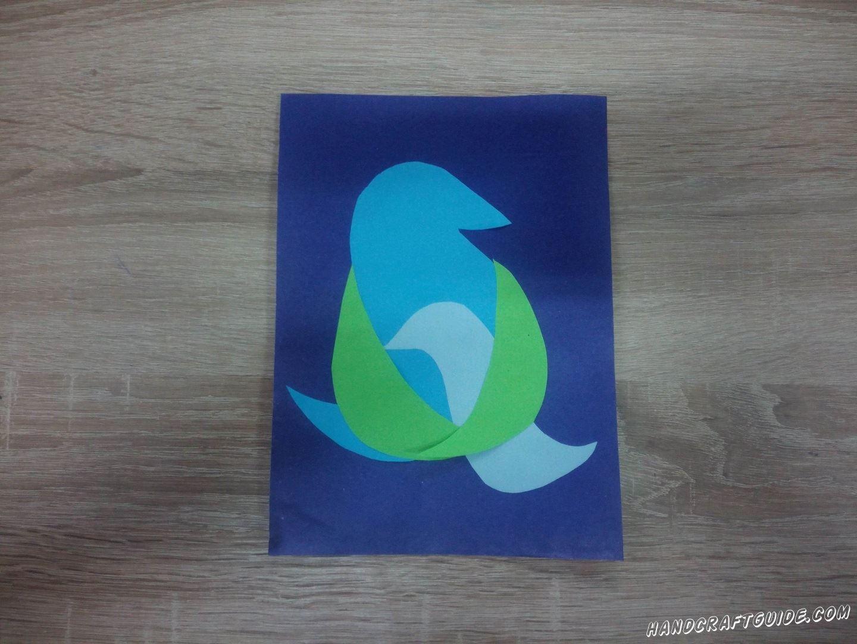 На синий фон наклеиваем самую большую нашу часть. Поверх наклеиваем светло-голубую детальку, чтоб верхняя часть была посередине большой птички. Затем приклеиваем крылышки для большой птицы, так как будто она обнимает своего ребёночка