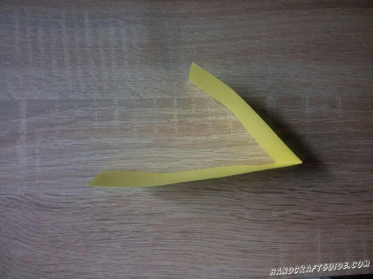 Затем врежем желтую полоску и сгибаем пополам немного ближе к одному краю