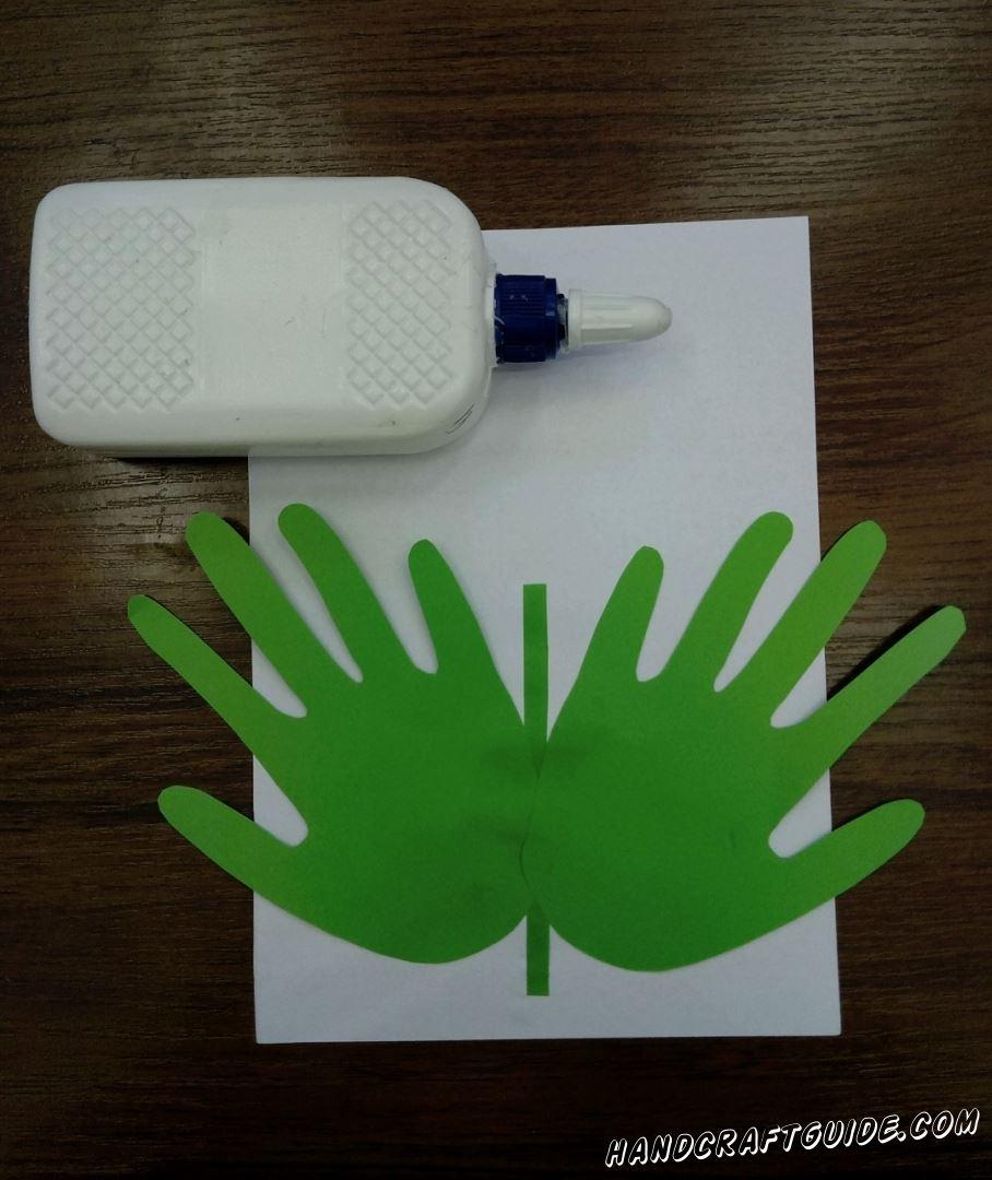 На белый лист наклеиваем зелёные детали в форме ладошек, а между ними тоненькую полосочку