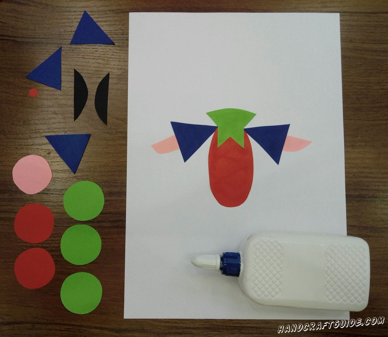 Приклеиваем наши детальки на белый лист бумаги. Сначала клеим красный овал. Затем приклеим зелёный воротник и рукава с ручками