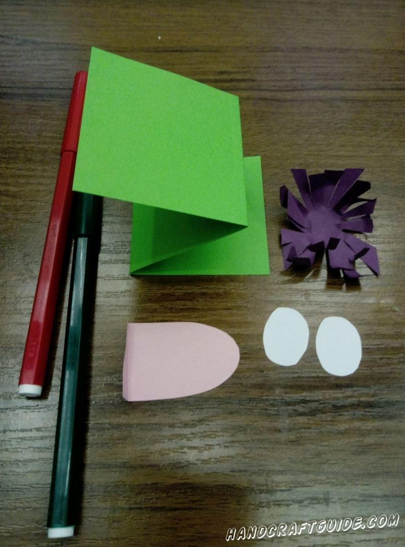 Из фиолетового квадратика , с помощью надрезов, делаем цвеочек. Из розовой вырезаем язычок. Ну и с белой бумаги,  маленькие овалы, это будут глазки.
