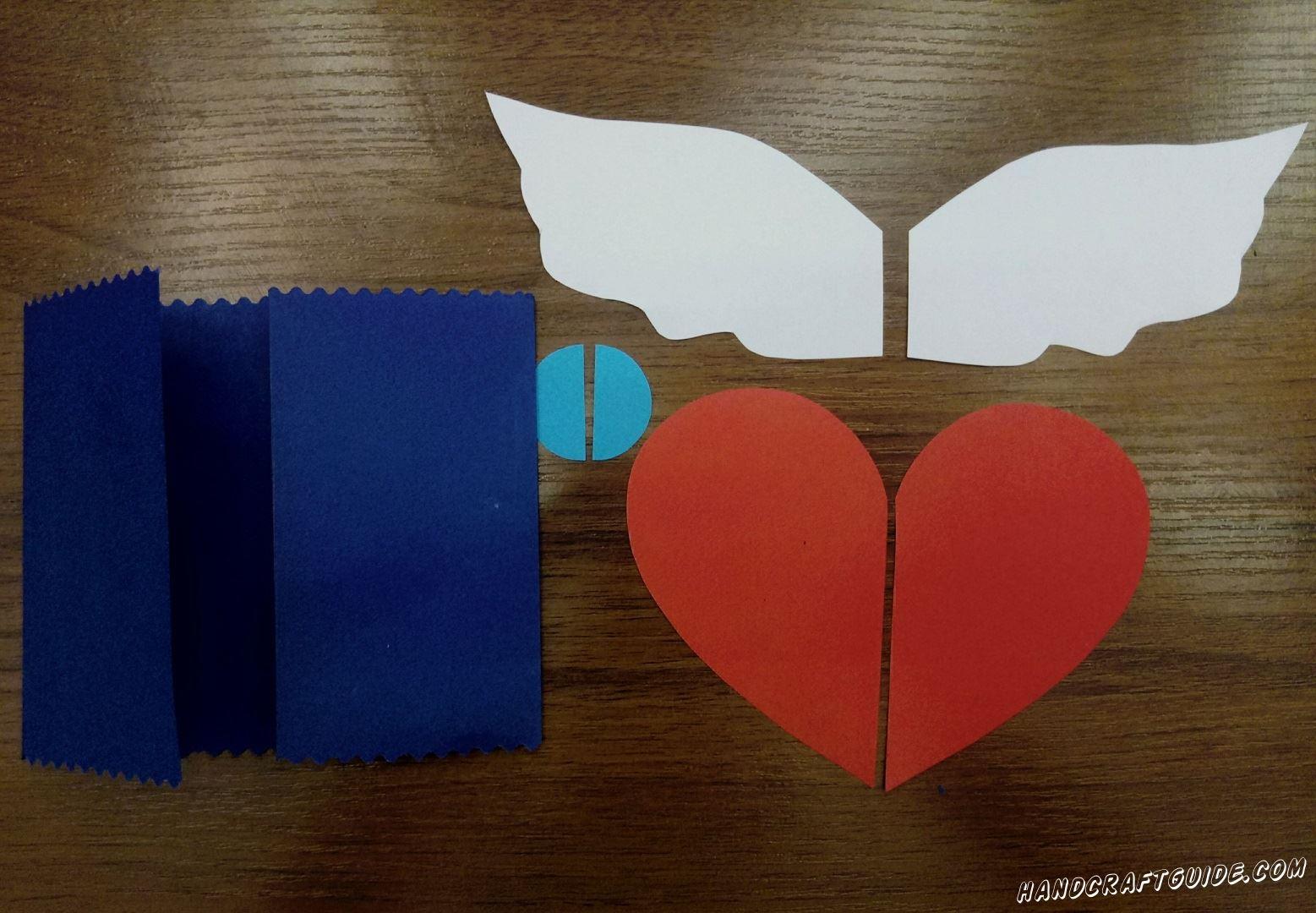 С помощью фигурных ножниц , придаем красивый вид по краям синего прямоугольника. Затем сгибаем его с двух сторон, чтоб их края сходились в центре