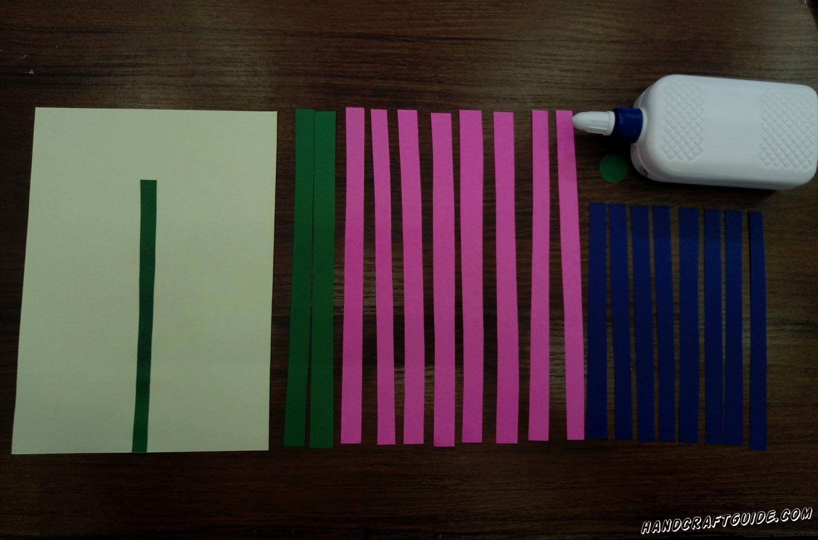 Берём бирюзовый , не порезанный, лист бумаги и приклеиваем на него короткую зелёную полоску, прямо по серединке. Молодцы
