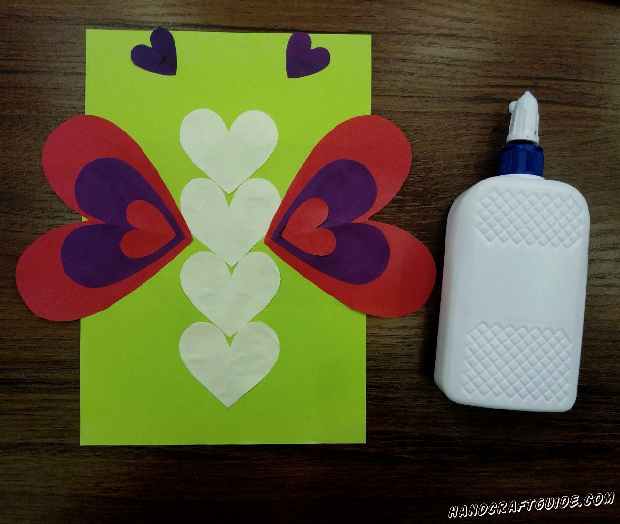 Take green sheet of paper and glue 4 yellow hearts one by one exactly in the middle of it. Between the second and the third hearts glue big red hearts on the sides. On top of them add large purple hearts and on top of them glue little red hearts. The main thing is not to get confused but the photo can help you. Above the butterfly glue 2 small purple hearts.