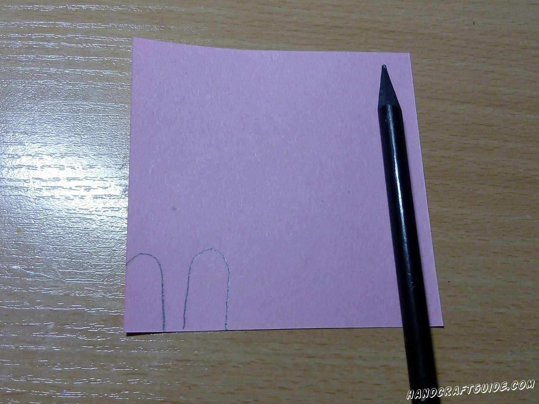 Затем берем листик фиолетового цвета и рисуем на нем 2 заячьих ушка. Вырезаем нарисованное