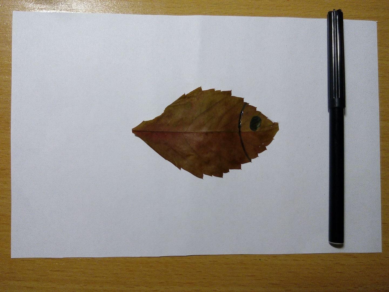 Теперь берем фломастер черного цвета и разрисовываем рыбку, воображая что листочек это тело рыбки.