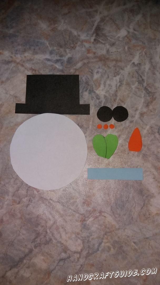 Сначала вырезаем все необходимые нам детали из цветной бумаги: большой белый круг, черная шляпа и 2 кружочка, голубая полоска, сердечко зелёного цвета, небольшая морковь и 3 очень маленьких кружочка оранжевого цвета.