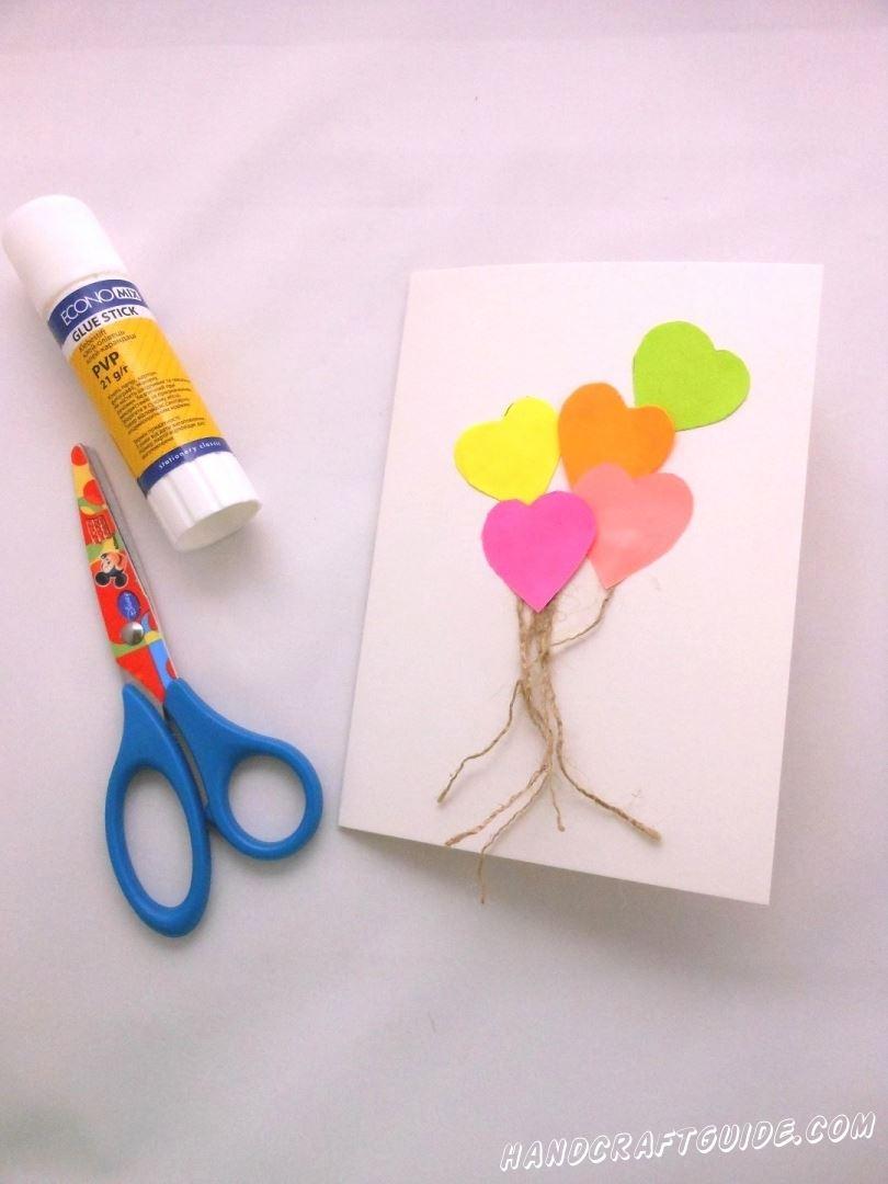 Снизу внешней стороны открытки мы прикладываем несколько ниточек, будто это верёвочки для воздушных шариков, а сверху наклеиваем наши сердечки.