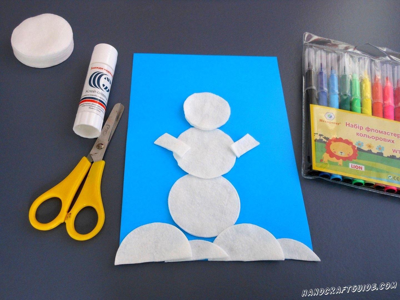 Берем ещё пару ватных дисков и разрезаем из них снег на низ поделки и 2 ручки снеговику.