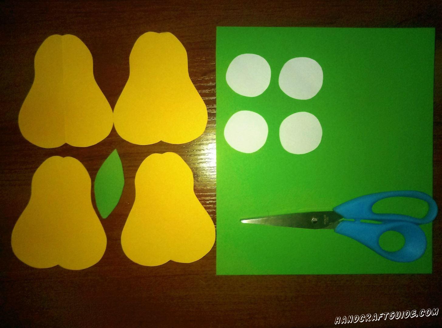 Из оранжевых прямоугольников вырезаем 4 одинаковые фигурки в форме груши. Лист зелёной бумаги скручиваем в трубочку и склеиваем. Из маленького зелёного кусочка вырезаем листочек. Затем берем коричневую бумагу и вырезаем 8 маленьких коричневых косточки
