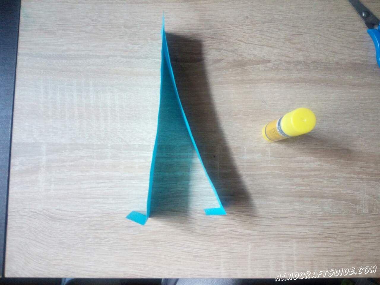 Склеиваем наши голубые полоски в одной стороне, а другую сторону немножечко загибаем