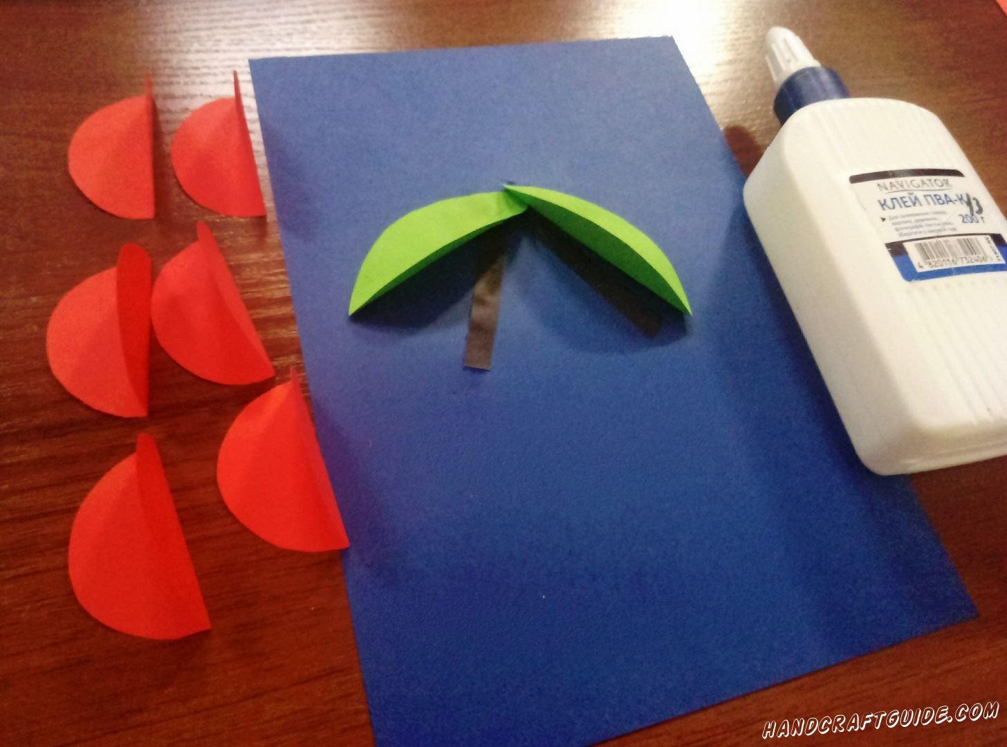 Из коричневой бумаги вырезаем 2 небольшие полосочки. Приклеиваем на синий фон листочки и коричневые стебельки