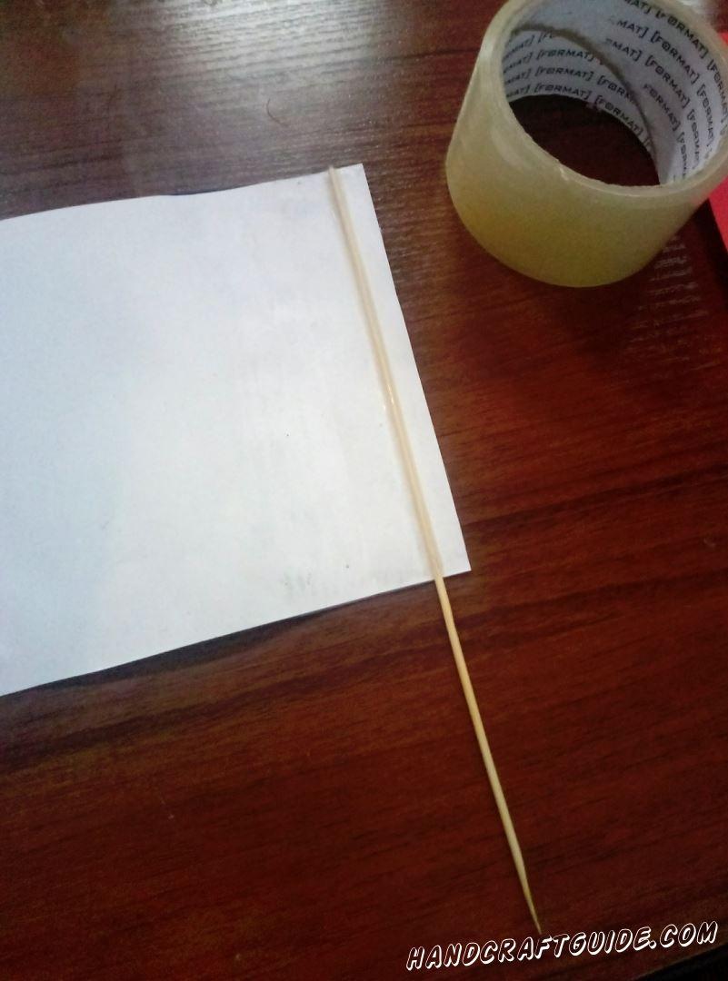 Затем переворачиваем нашу подделку и с одной из сторон приклеиваем шпажку, с помощью скотча.