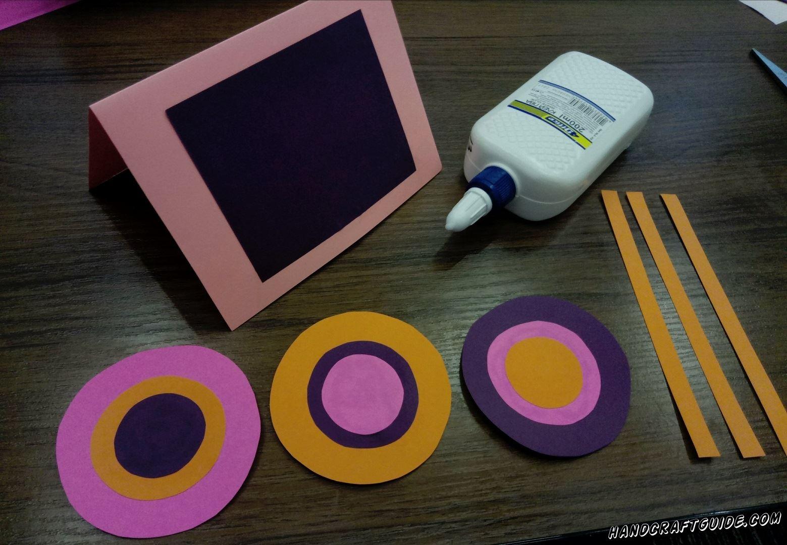 Берём розовый лист и сгибаем его пополам и ставим как подставочку и на одну половинку приклеиваем фиолетовый прямоугольник, но клеем только по краям, чтобы верхняя часть была открыта, а а внутри прямоугольник не было приклеено, своего рода конвертик
