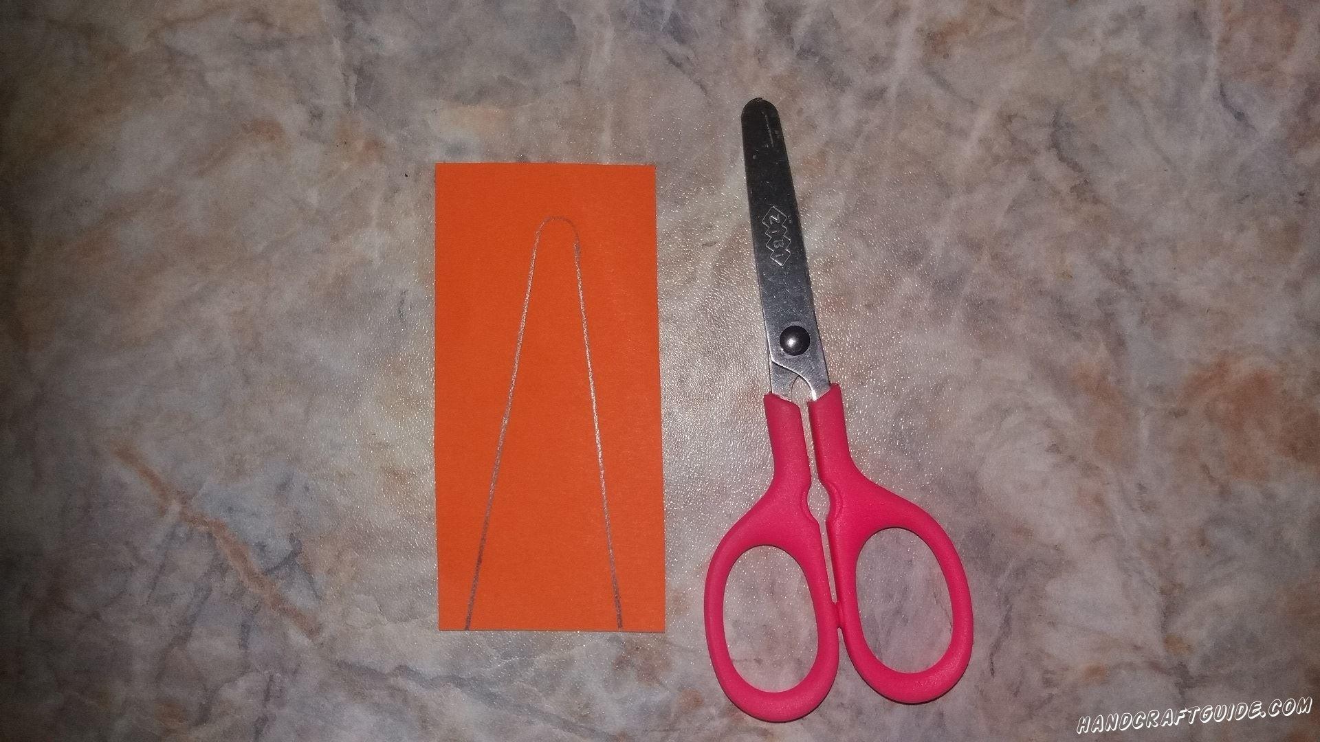 Затем берем оранжевую бумагу и вырезаем фигурку в форме морковки.