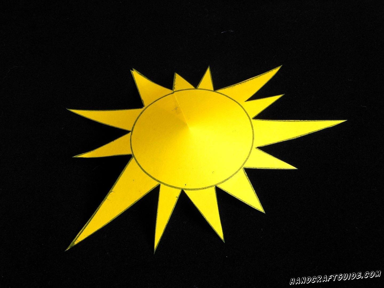Теперь делаем аккуратный надрез прямо к центру кружечка нашего солнышка. Подтягиваем один обрез под второй на расстояние одного лучика и склеиваем в таком положении. Полученная фигурка напоминает шапочку.