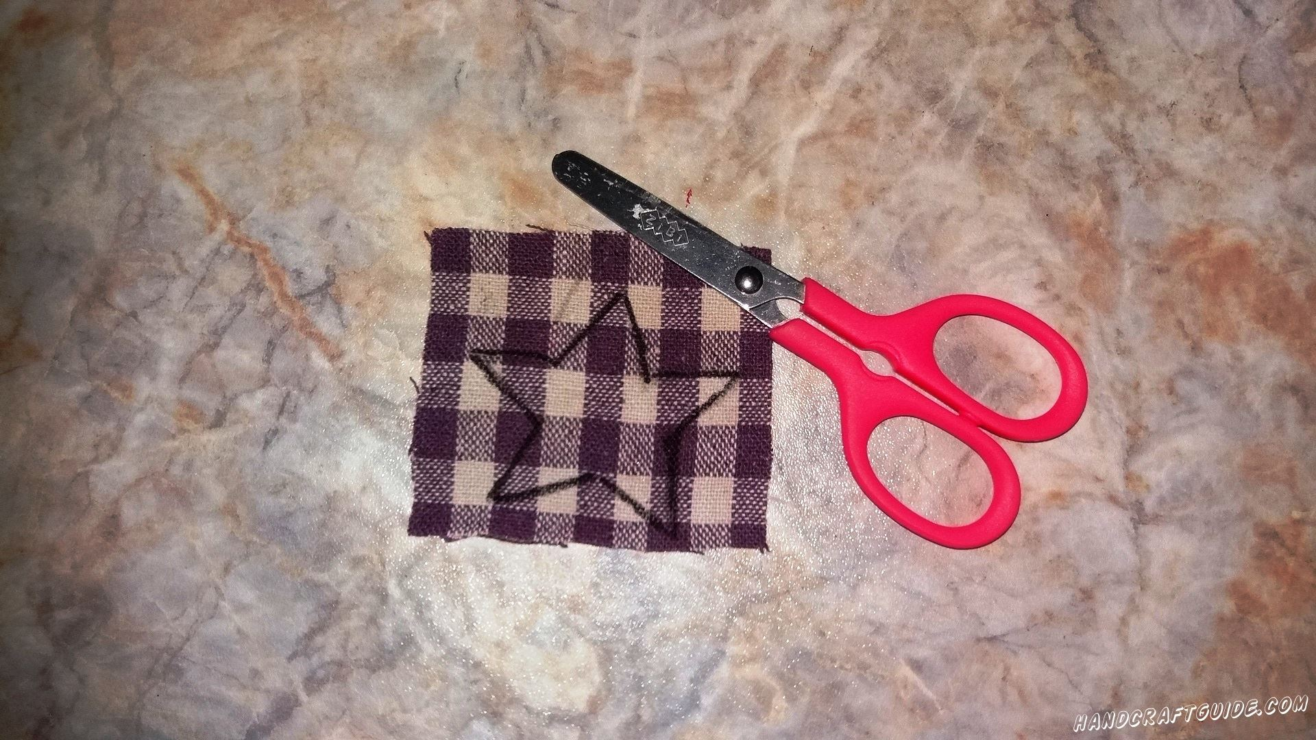 На другом кусочке ткани мы рисуем звёздочку и так же вырезаем её.