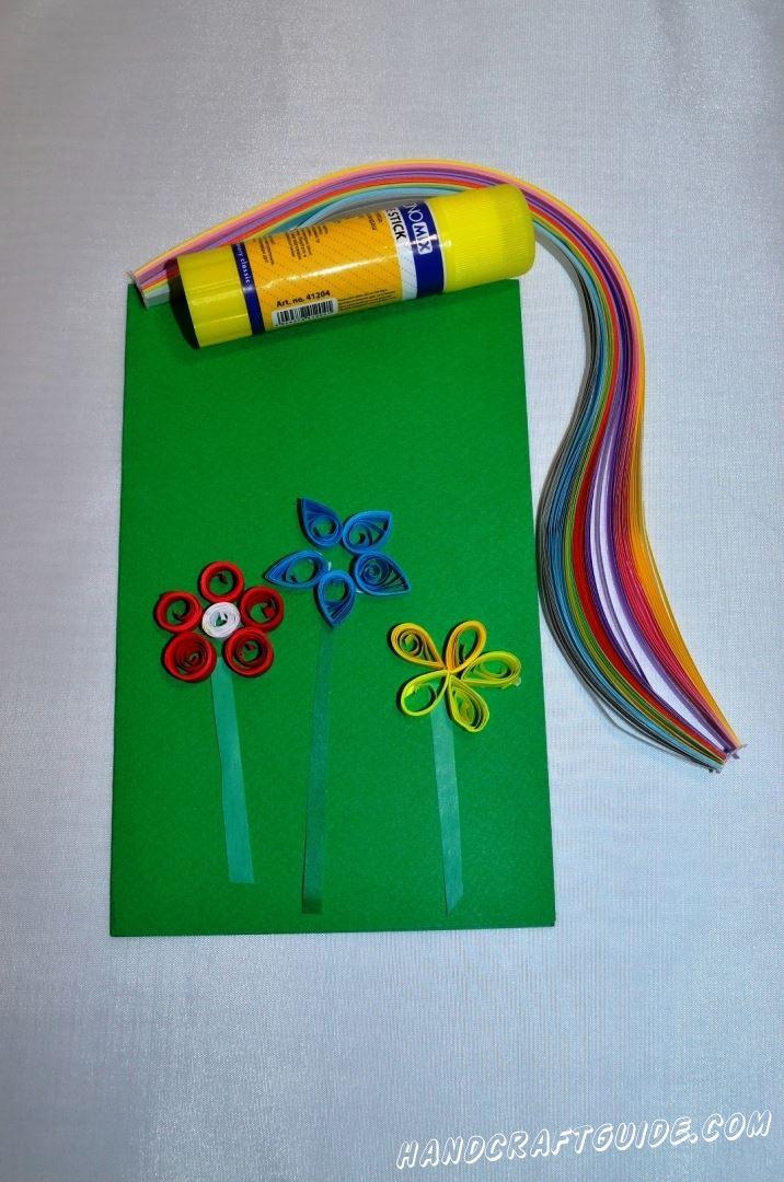 Затем делаем таким же образом и желтый цветочек, только острые концы мы склеиваем внутрь. Теперь приклеим зелёные стебельки.