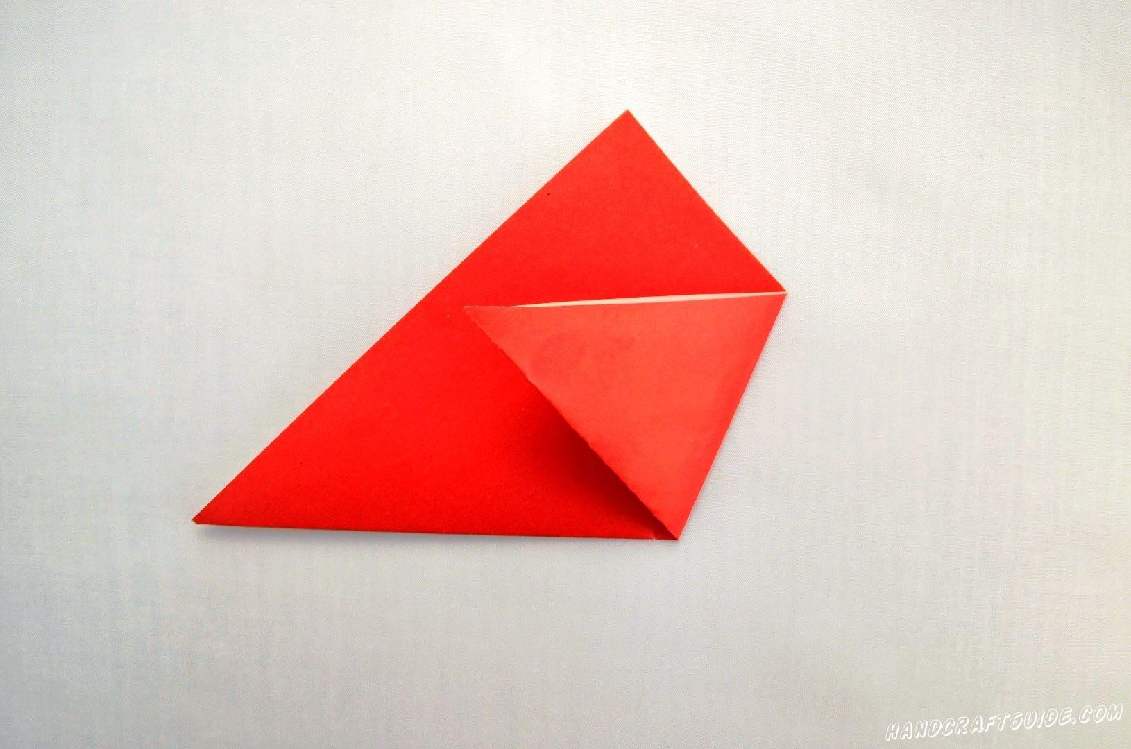 Затем загибаем два дальних угла нашего треугольника к центру