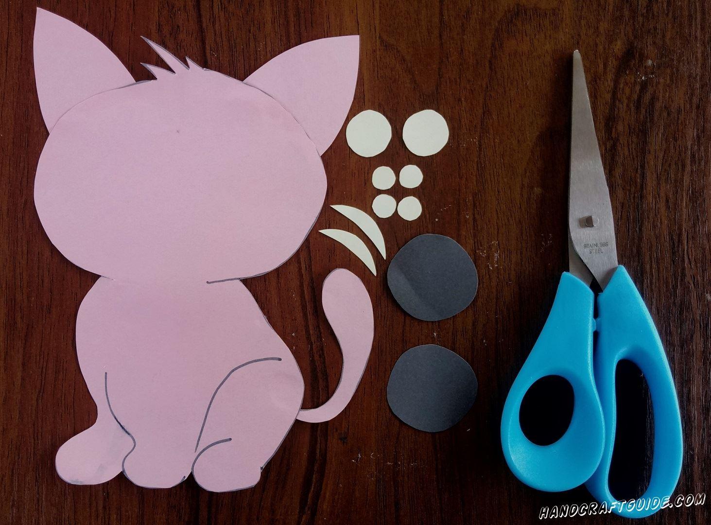 Затем берем бумагу черного цвета и вырезаем 2 круга. А из белой бумаги вырезаем 2 маленьких кружка,4 совсем маленьких круга и 3 скобочки.