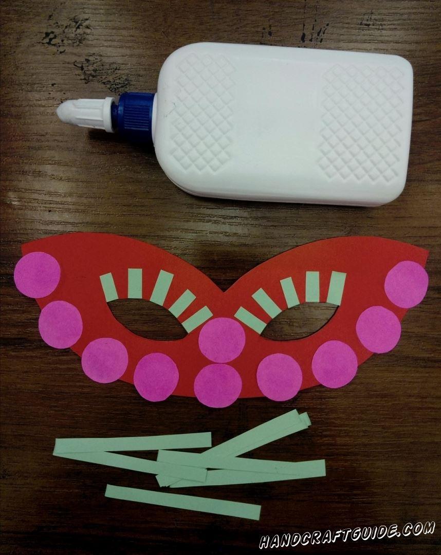 Берём кружочки и приклеиваем по нижней части маски, а один кружочек прямо между отверстий для глаз.