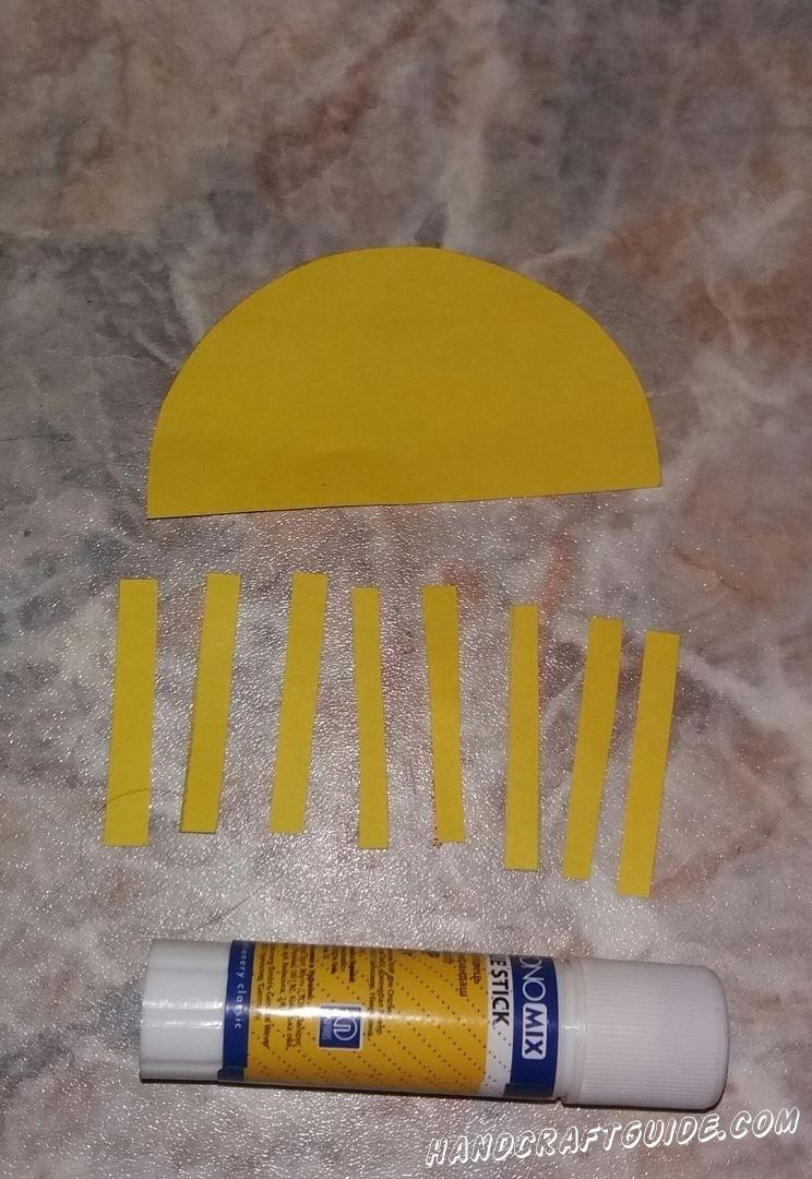 Приклеиваем желтые лучики к закругленной стороне солнышка