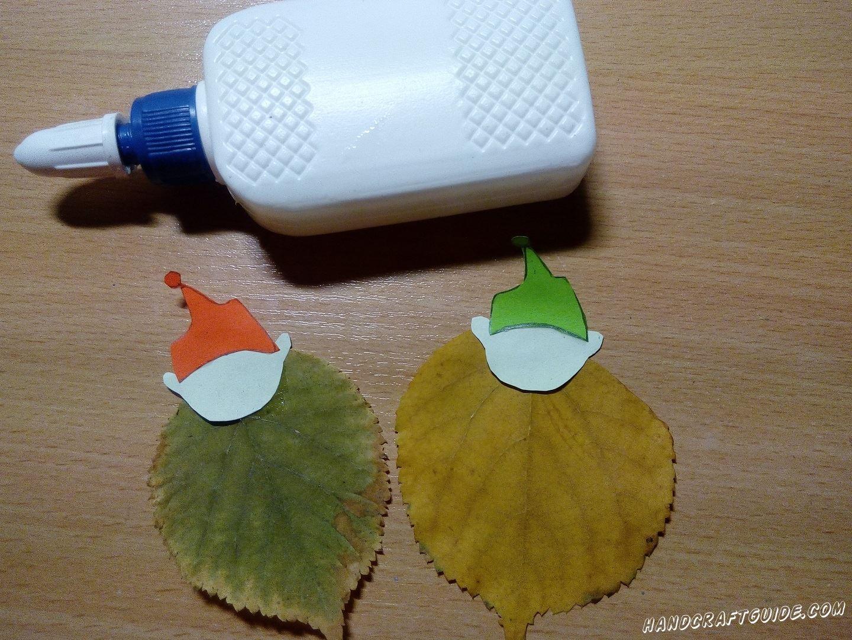Затем берем 2 листа с деревьев и приклеиваем по 1 голове с шапочкой на каждый. Приклеиваем вертикально на широкой стороне листика