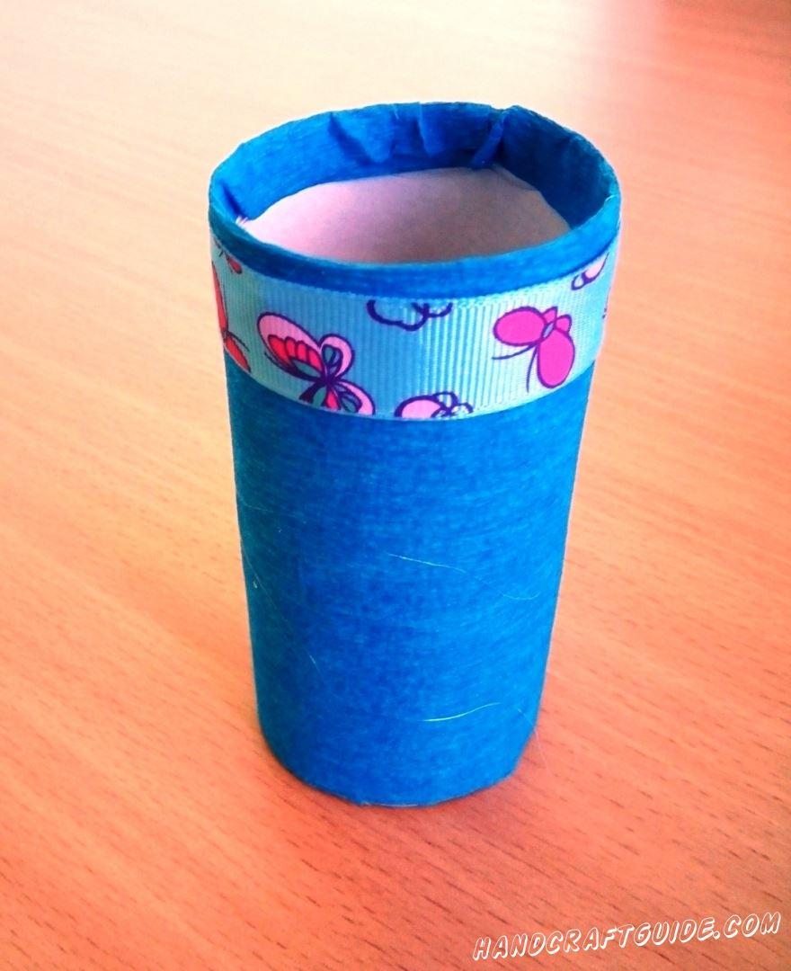 Накручиваем три полоски розового цвета на карандаш и снимаем, получая кудряшки из бумаги. Приклеиваем их к нижней части вазы. Осталось только наполнить нашу поделку ватой и поставить в неё цветочки.